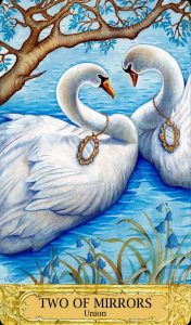 Two swans face each other, an oval mirror on a chain around each of their necks