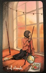 A person sits, looking out a window, with a globe beside her and two wands, taller than she.